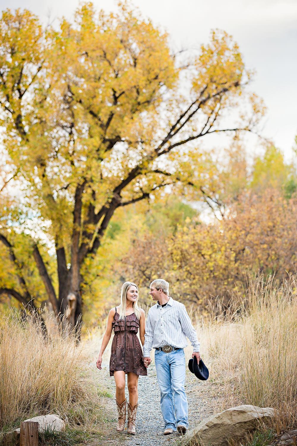 Billings-Montana-fall-engagement-woman-walks-through-park-with-her-cowboy.jpg