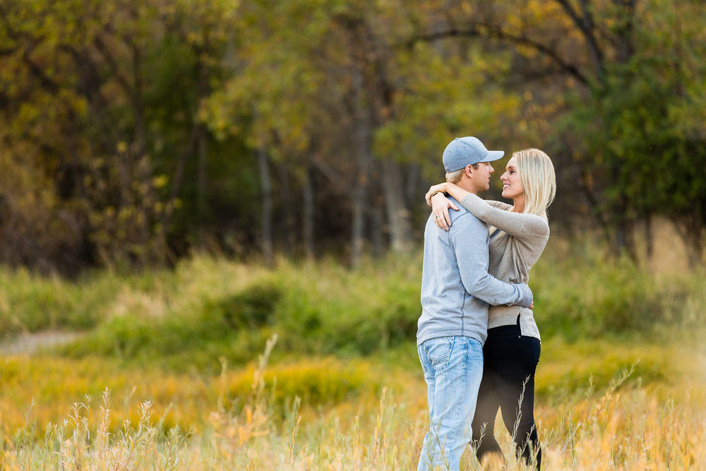 Billings-Montana-fall-engagement-woman-wraps-her-arms-around-man.jpg