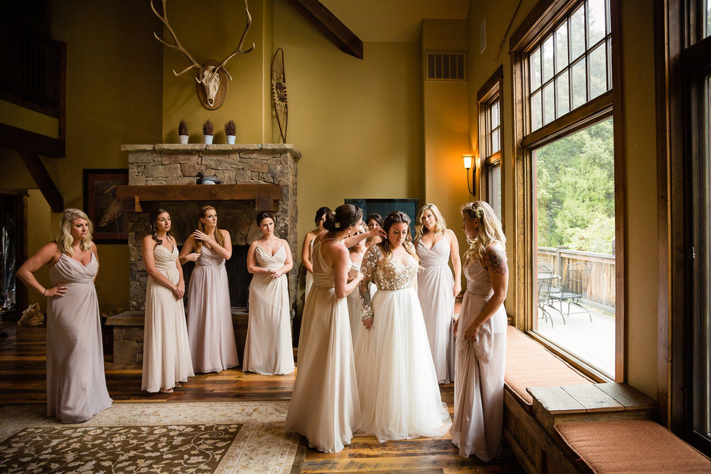 bozeman-hart-ranch-wedding-bridesmaids-help-bride-get-dressed.jpg
