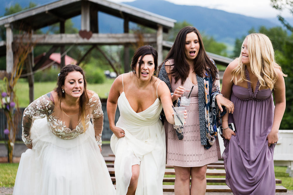 bozeman-hart-ranch-wedding-bride-jumps-off-bench-with-friends.jpg