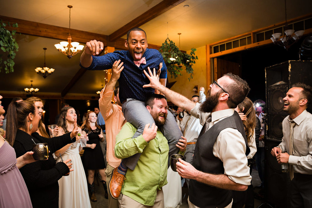 bozeman-hart-ranch-wedding-guests-dance-with-man-on-shoulders.jpg