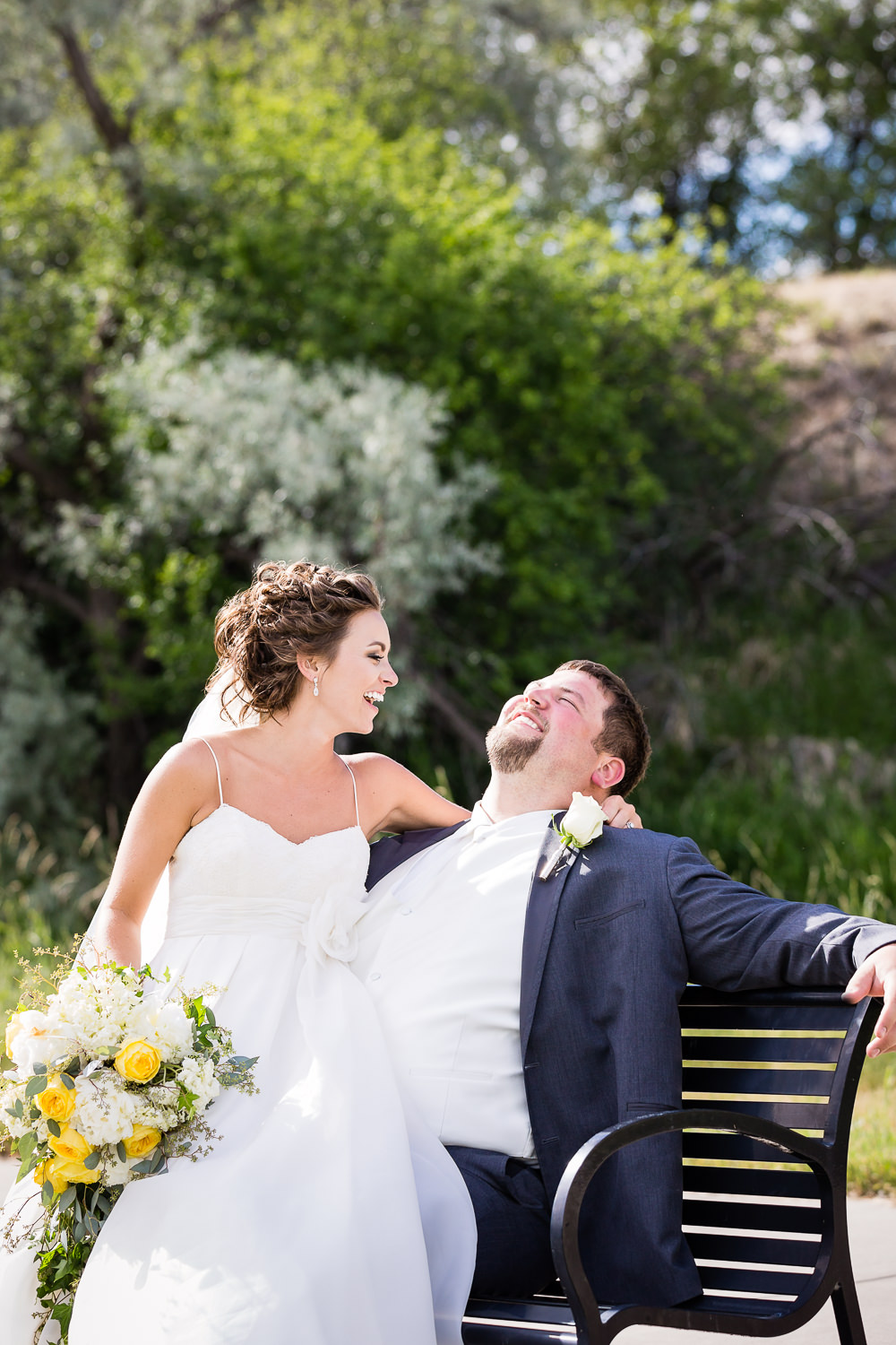 billings-montana-swift-river-ranch-wedding-reception-couple-laughing-on-bench.jpg