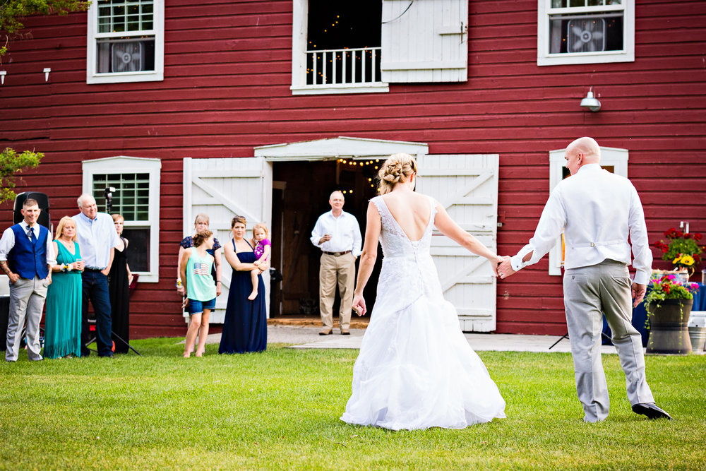 bozeman-montana-wedding-roys-barn-bride-groom-hold-hands-during-reception.jpg