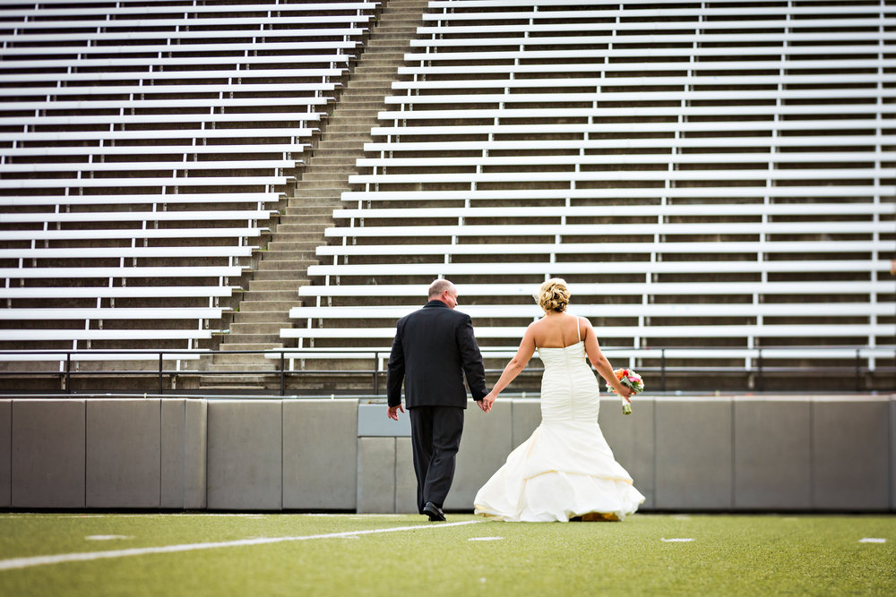 missoula-museum-mountain-flying-wedding-first-look-walking-on-football-field.jpg