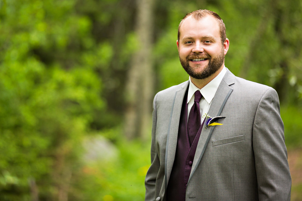 rock-creek-resort-red-lodge-groom-smiling-in-forest.jpg