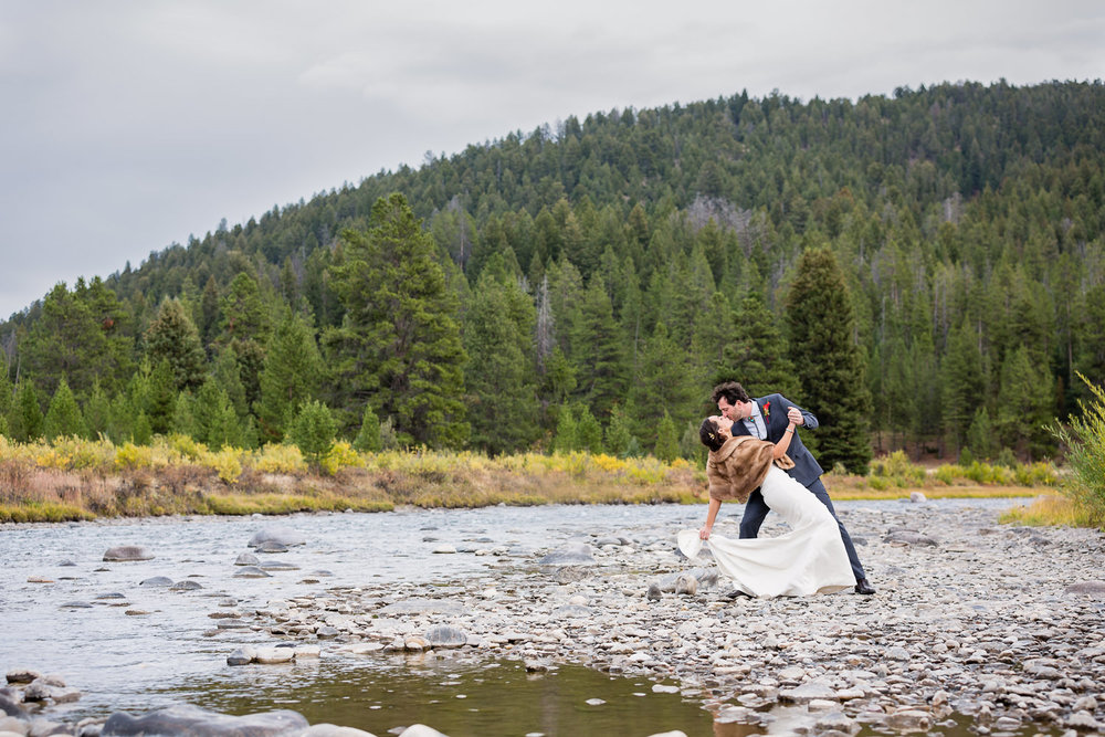 big-sky-montana-gallatin-riverhouse-wedding-groom-dips-bride-next-to-riverbank.jpg