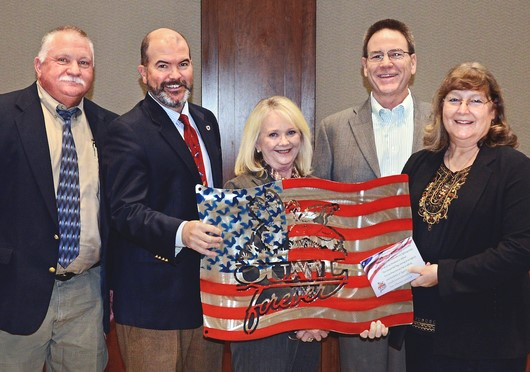 Presenting metal artwork used to raise funds for the Wildlife Department's Stars & Stripes License Project are, from left, Department Wildlife Chief Alan Peoples, Department Director J.D. Strong, Department Assistant Director Melinda Streich, James Dietsch and Laura McIver, both of Central Oklahoma Quail Forever.