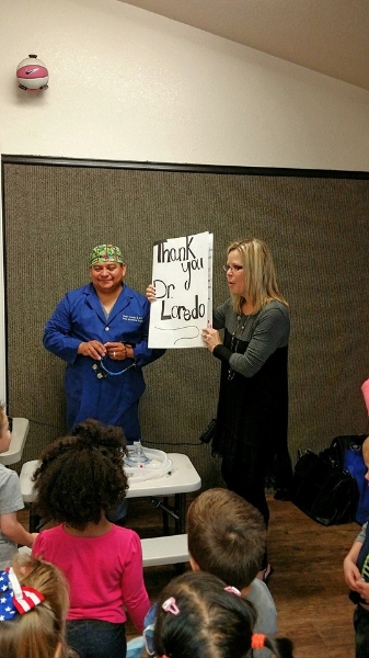 Hand surgeon, Dr. Loredo accepting a thank you card from the kindergarten class.
