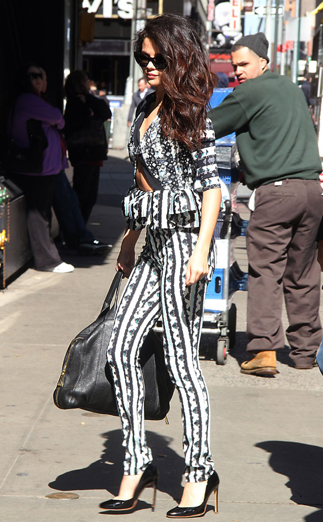 SELENA GOMEZ For an appearance on Good Morning America in New York, the brunette beauty dons a Peter Pilotto Lara top featuring a cutout detail and ruffled peplum with matching pants. She accessories her printed attire with a black oversize handbag and Rubert Sanderson Troy pumps.
