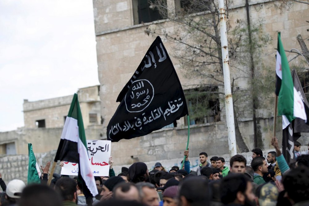 """Protesters carry Al-Qaeda and Free Syrian Army flags during an anti-government protest... in Idlib province, Syria, March 11, 2016."" Courtesy of  Newsweek . KHALIL ASHAWI/REUTERS"