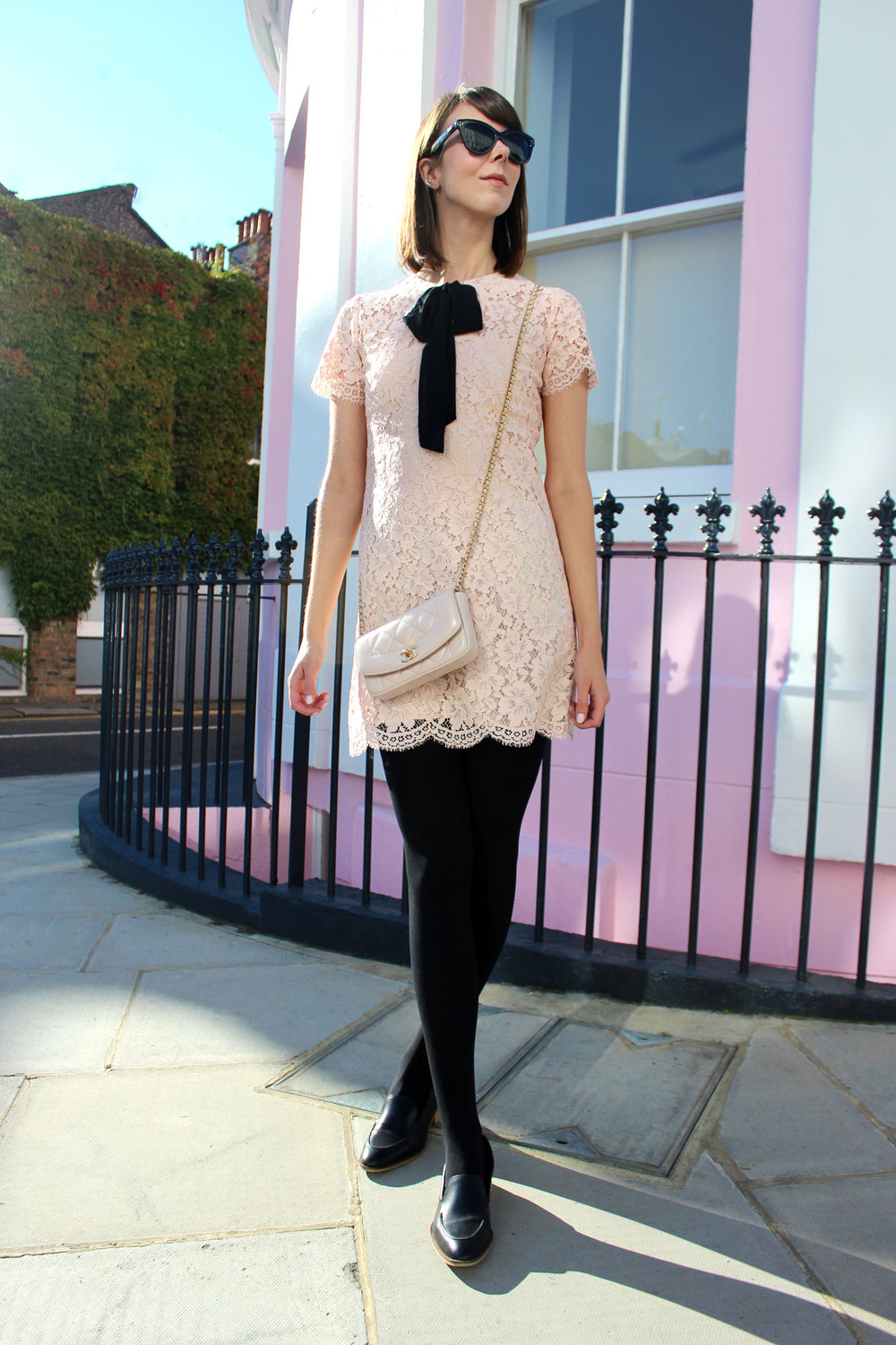 Blush pink Sandro dress with black bow paired with opaque black tights