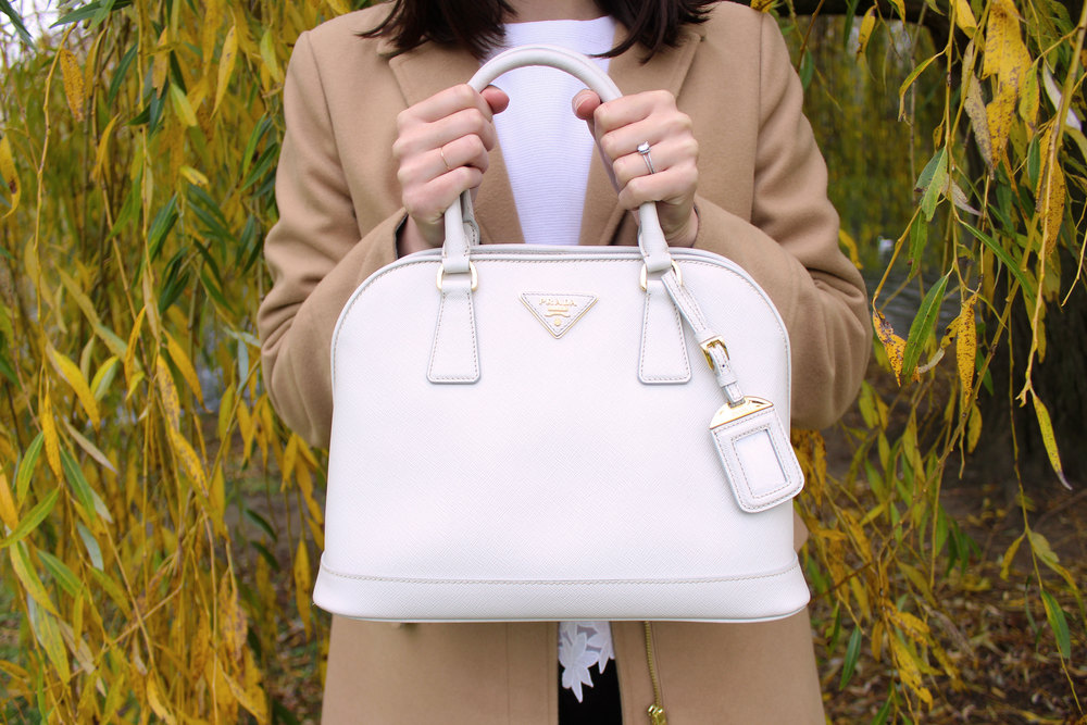 White leather Prada bag paired with a camel coat from Topshop.