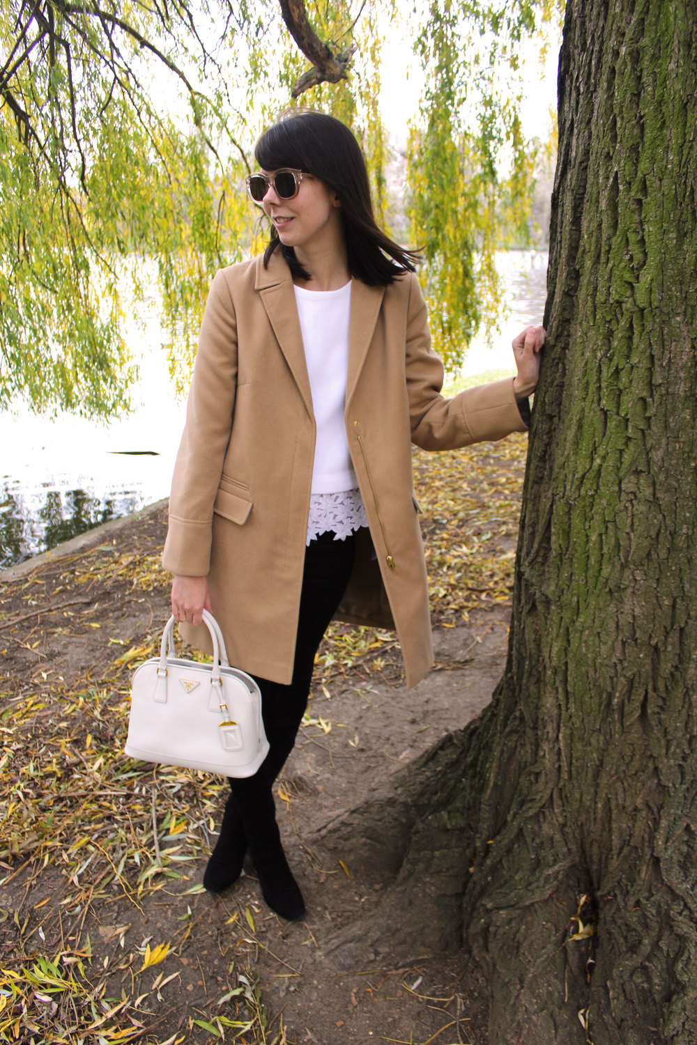 Standing beneath the willow trees in Regent's park wearing suede over the knee boots, a camel coat, and a Prada bag.