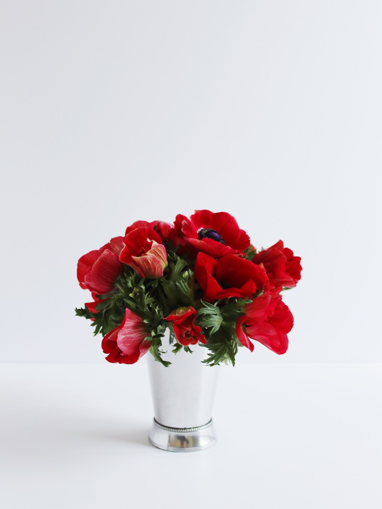 Red anemone flowers in a silver mint julep cup make a cute floral centerpiece for derby day.