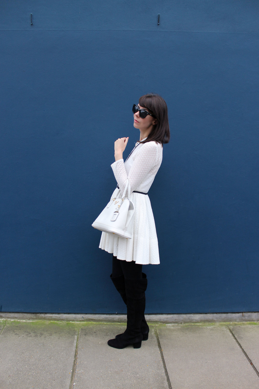 Wearing a white lace Maje dress and suede over the knee boots in Notting Hill.
