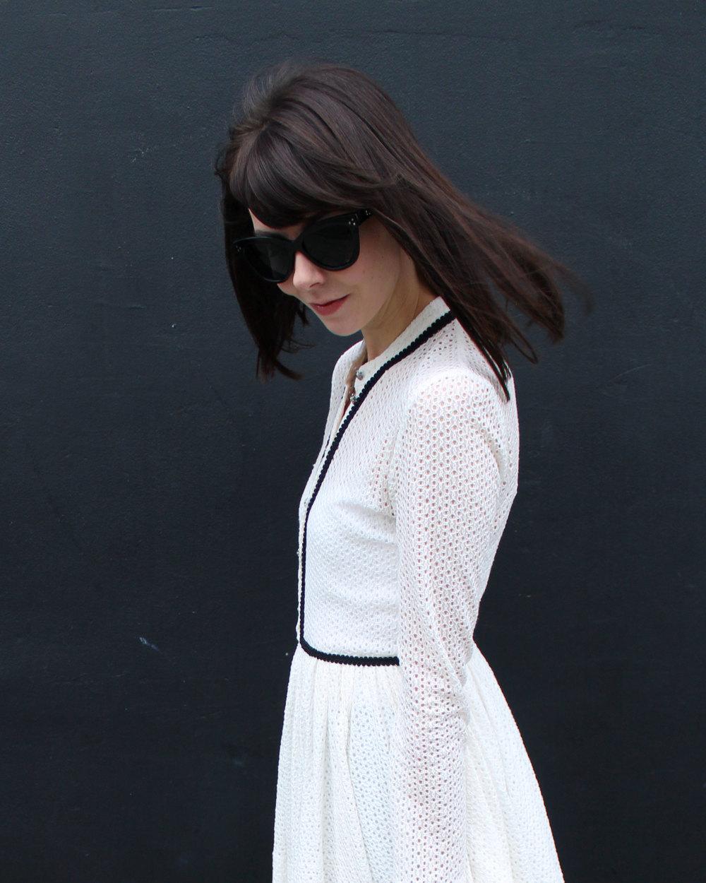 Wearing a white lace Maje dress and oversized black sunglasses.