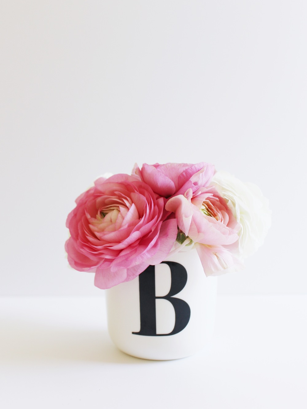 Pink and white ranunculus flowers in a monogrammed bud vase.