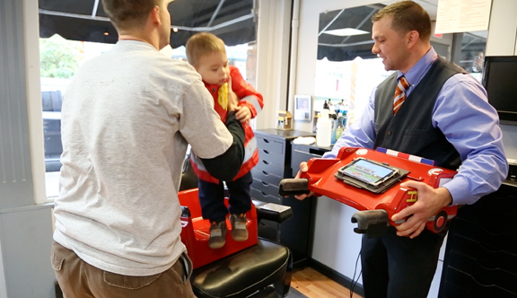 After the haircut is finished, clean off the child, remove the tray and have the parent safely remove the child.