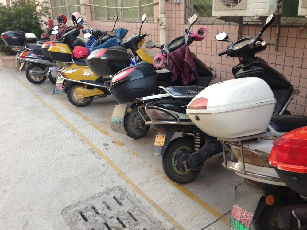 Production line workers' scooters outside the textiles factory in China
