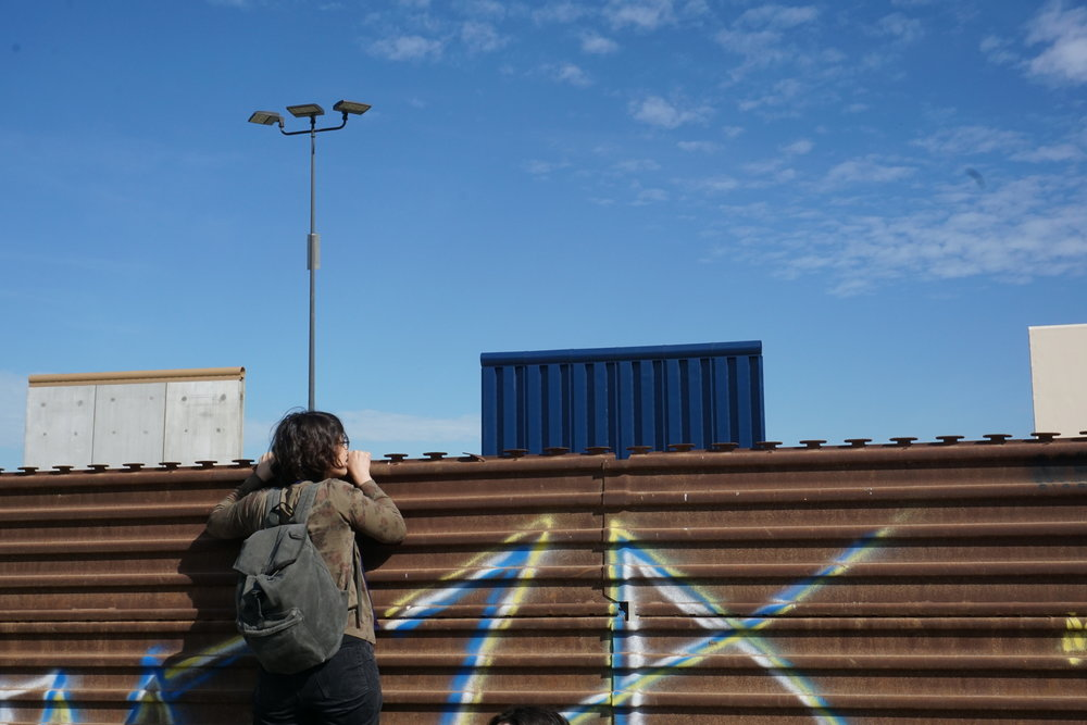 Helia peering over the wall to see the prototypes from the Tijuana side.