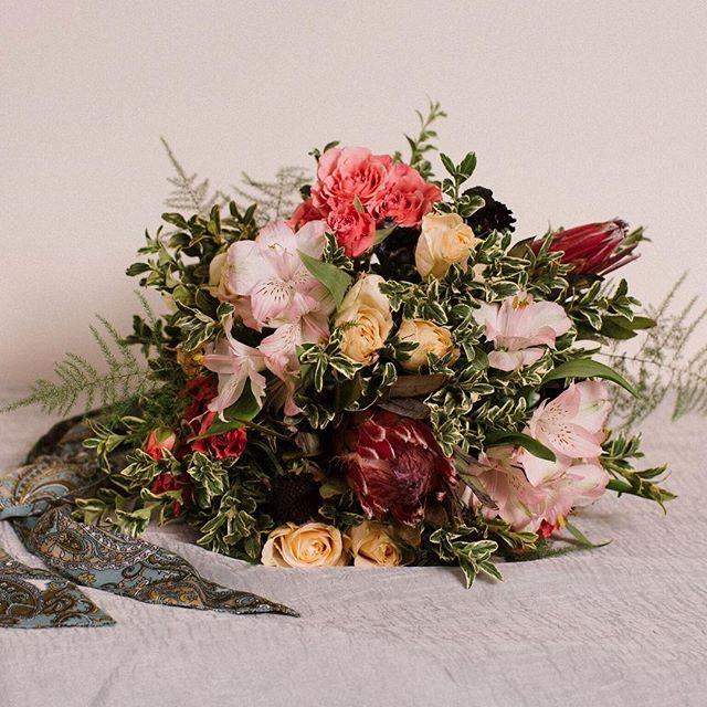 Hand tied bouquet with protea, roses and alstroemeria / Image by @solidityfilms