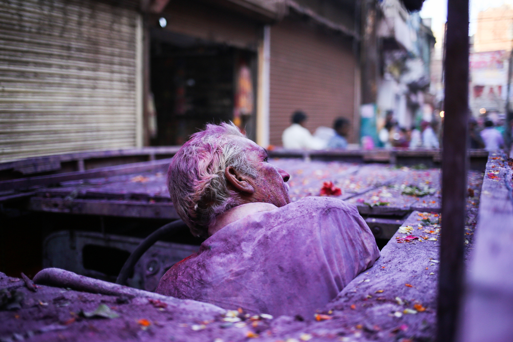 Vrindavan, India - March 23rd, 2016: A man is covered with color on the day before Holi actually starts. Mathura tends to get very festive weeks before Holi.