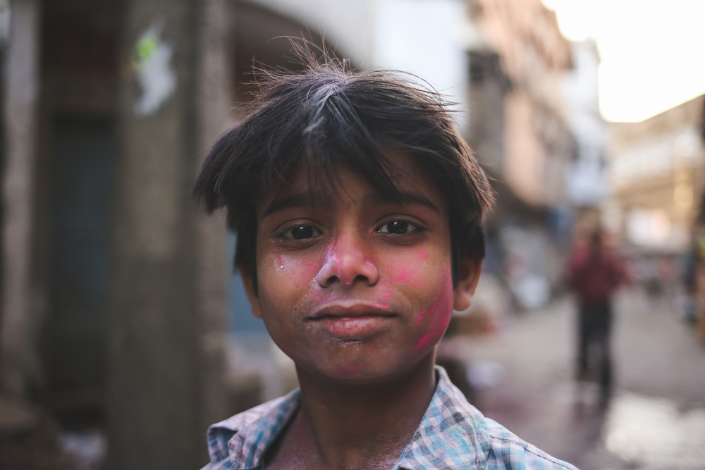Mathura, India - March 24  th, 2016:  A young boy poses after getting hit by gulal from his friends.
