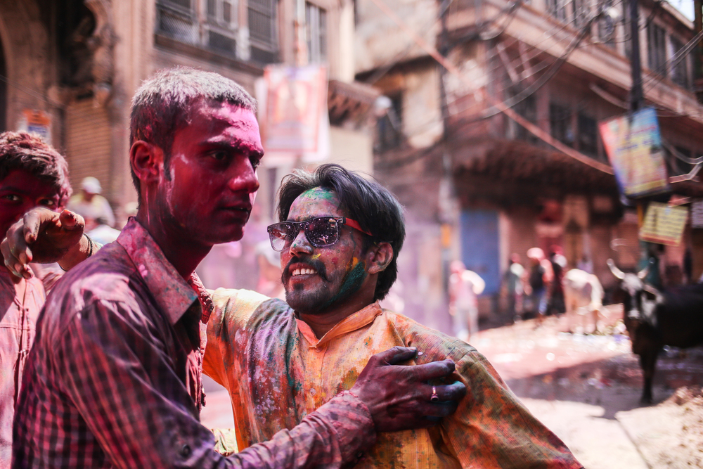 Mathura, India - March 24th, 2016: Two friends hug after getting gulal powder thrown all over them by strangers at one of the major spots of festivities.