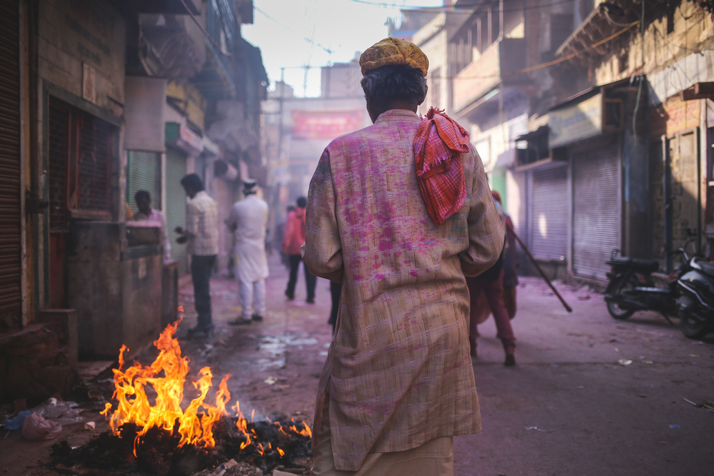 Mathura, India - March 24th, 2016: A man walks towards a fire towards the end of Holi.