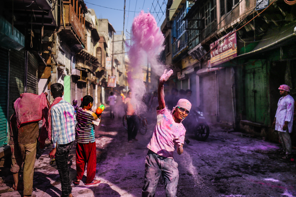 Mathura, India - March 24th, 2016: A boy throws gulal to celebrate Holi.