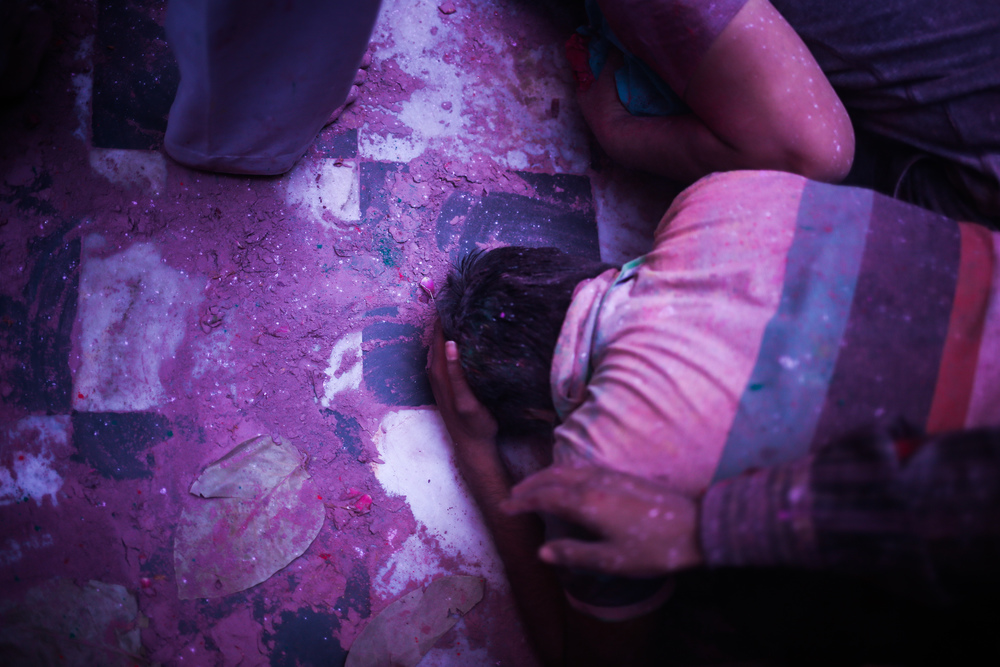 Vrindavan, India - March 23rd, 2016: A man throws himself to the ground with emotions as he prays in a temple the day before Holi