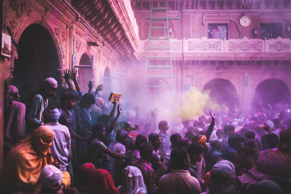 Vrindavan, India - March 23rd, 2016: Many people enter the temple throwing gulal into the air to celebrate Holi.