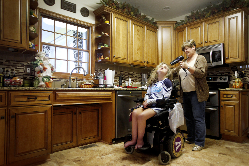 Vicki Lezon dries her daughter's hair in their kitchen before heading to a cheerleading performance Saturday, November 2.