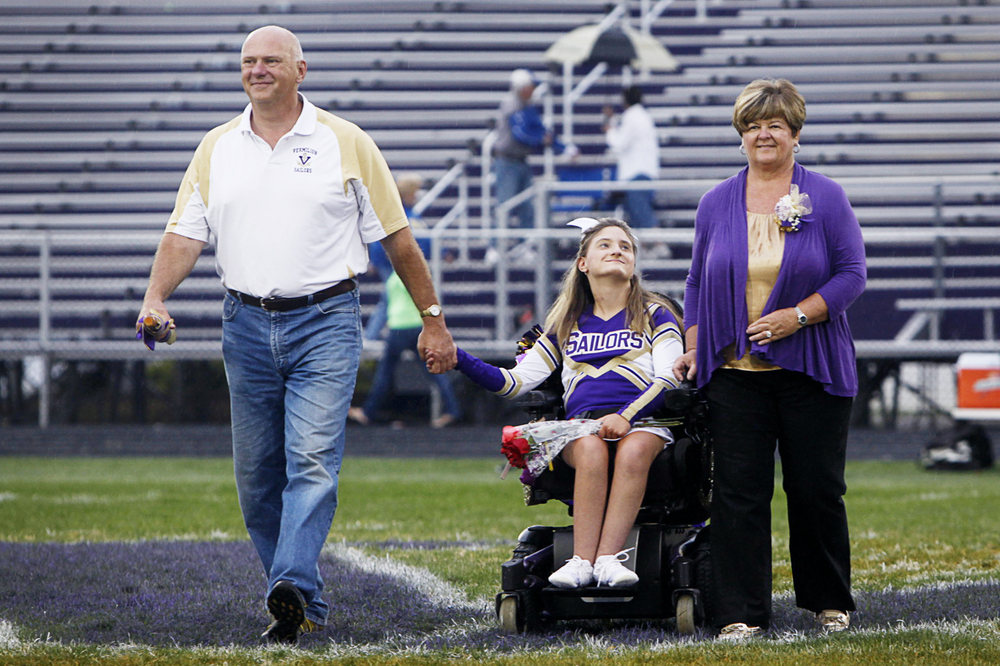 Emily looks up at her mother, Vicki, as she crosses the field with her and her father, Todd, during senior night at Vermilion High School Friday, October 4.