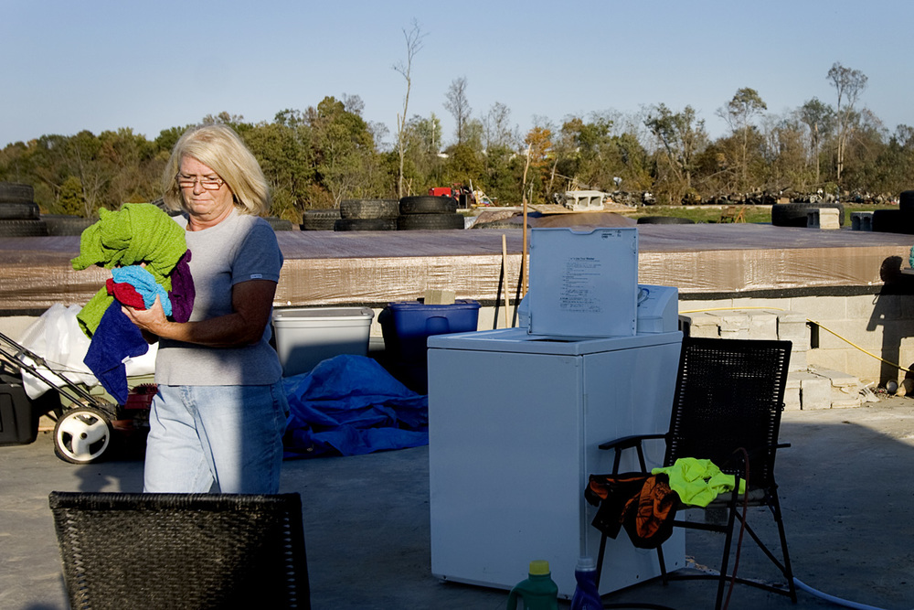 "Shirley transfers her wet laundry to her dryer on the concrete pad of her garage, the only evidence of her former home. ""A girl's gotta do what a girl's gotta do,"" she laughed at her setup."