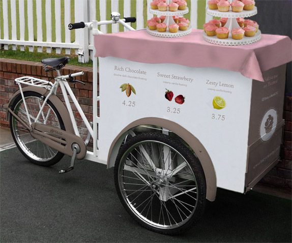 "Cupcake Bike / A traveling cupcake bike promotes more health than a food truck. Illustrations of the ingredients are used instead of pictures of each type of cupcake for the bike menu, emphasizing the all-natural organic cupcakes. On the front side: ""Follow me on Twitter! @BabycakesNYC"""