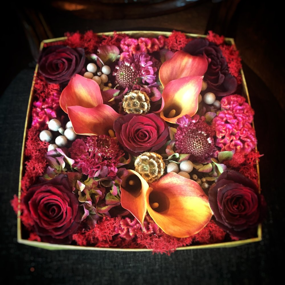 Designer's choice with mango callas, black baccara roses, antique hydrangea, silver brunnia, scabiosa pods, scabiosa blooms, and burgundy celosia.