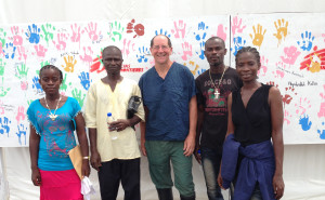 Dr. Daniel Lucey, center, poses with Ebola survivors in Monrovia, Liberia, in front of a wall featuring the hand prints of survivors.