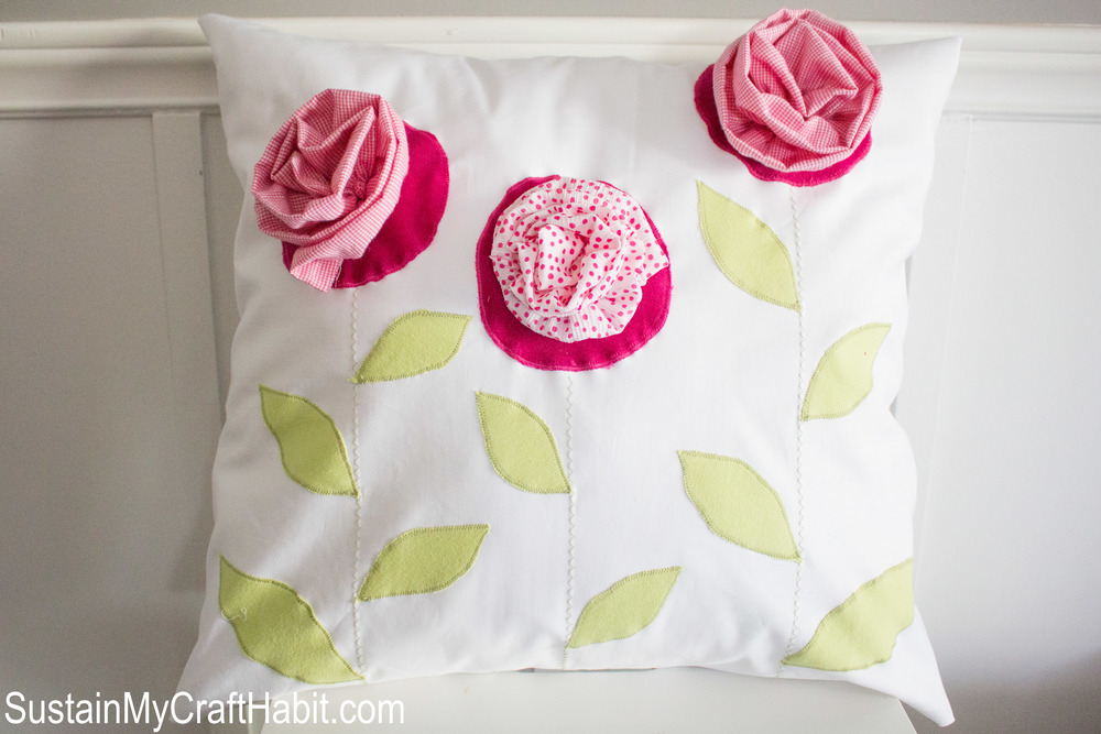 DIY throw pillow upcycled from outgrown baby clothing. This beautiful and bright home decor cushion would make a lovely keepsake or gift. Click through for the full tutorial.