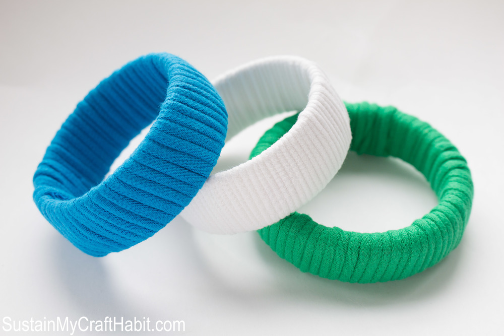 DIY T-shirt yarn restyled plastic bangles. A fun upcycling project idea using outdated jewelry and brightly colored t-shirt yarn. Click through for the step-by-step tutorial. SustainMyCraftHabit.com