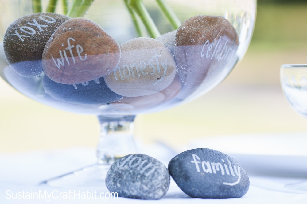 Beach stones and fresh-cut flowers create a stunning and inexpensive wedding or other special event centerpiece. Write memorable words on each stone in place in a clear vase. Click through for the tutorial and beautiful photos.  SustainMyCraftHabit.com