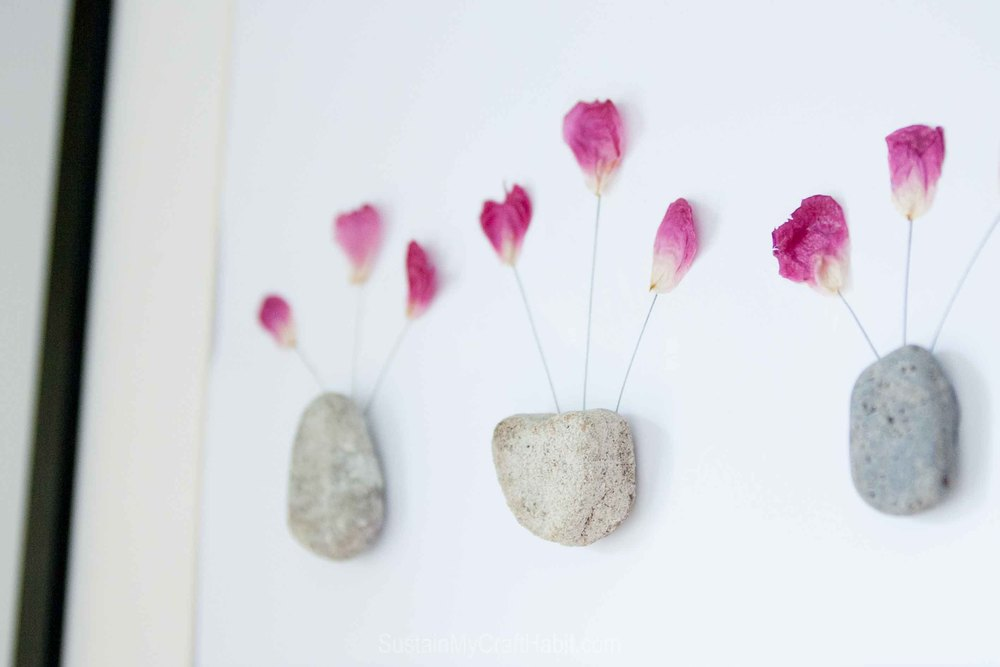 Make unique nature-inspired art for the wall with pressed flowers and rocks. Click through for the full step-by-step tutorial and child's comment that inspired this home decor idea. SustainMyCraftHabit
