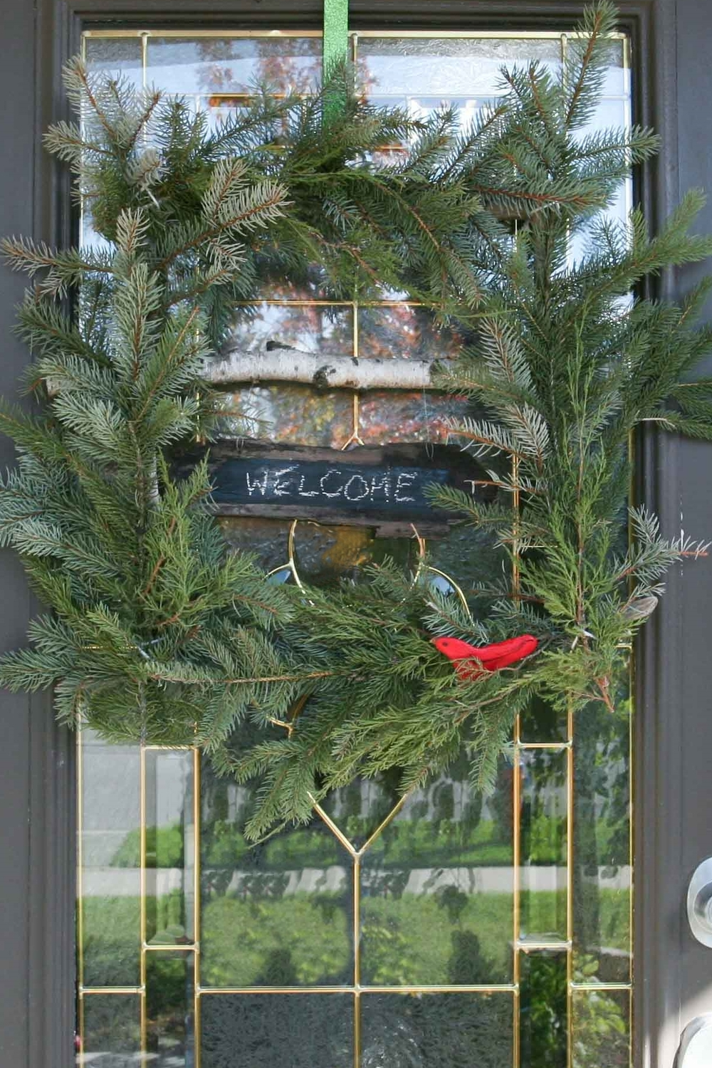 Bird on a window wreath: a square wreath made with a drfitwood and birch branch frame and covered in evergreen branches - SustainMyCraftHabit