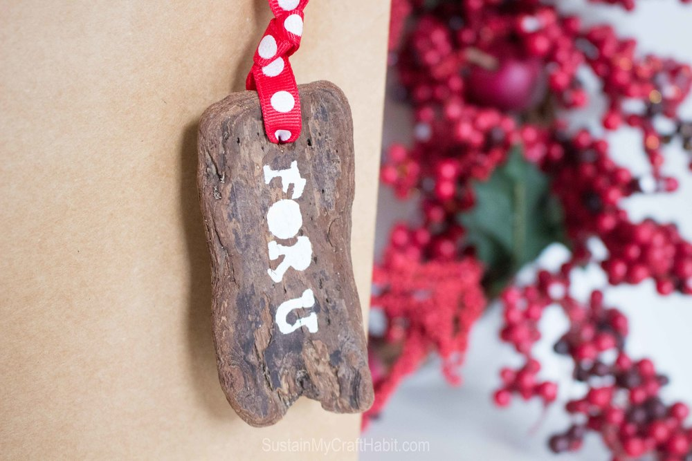 Up your gift-giving game with a natural and rustic DIY stenciled bark gift tag @SustMyCraft