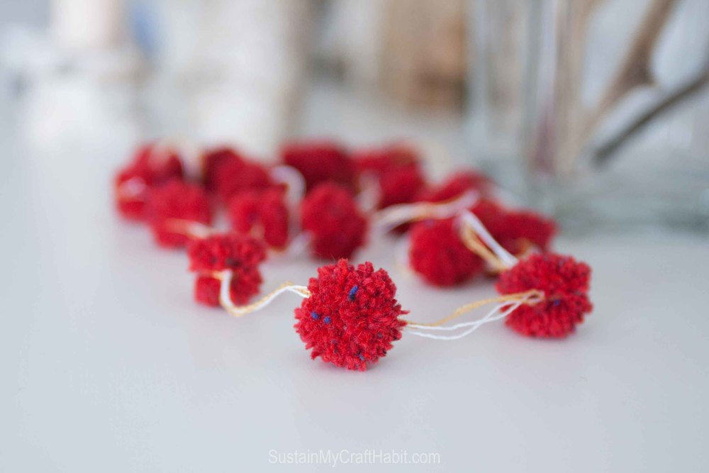 DIY decorative pom pom garland made with red yarn scraps. A contemporary decor idea for Christmas, Valentines or change up the yarn color for a wedding, shower, baby shower or other special event. - SustainMyCraftHabit