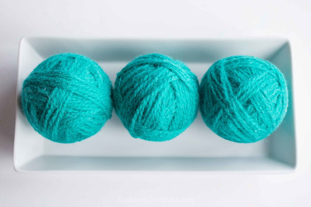 Add beautiful decorate pops of colour to your fronch porch greenery decor with easy DIY yarn balls by Sustain My Craft Habit. A step-by-step tutorial is included.