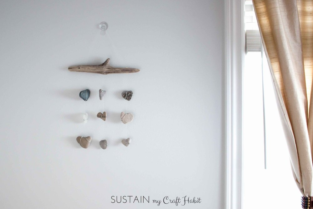 "Heart-shaped stones and sea glass collected on the beach are strung with a piece of driftwood to make this nautical decor piece: a ""Heart of Stone"" coastal mobile. Follow the step-by-step tutorial for this rustic DIY wall hanging idea."