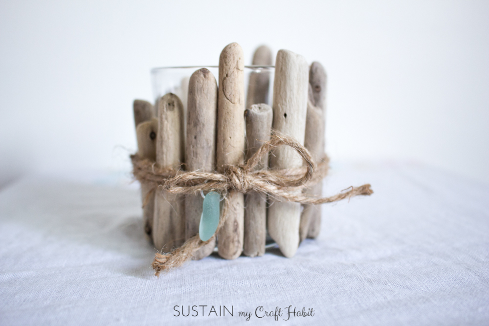 Upcycle standard glass votive candle holders with driftwood pieces. A really simple DIY idea that would be lovely for a rustic or coastal wedding. Click through for the full instructions.