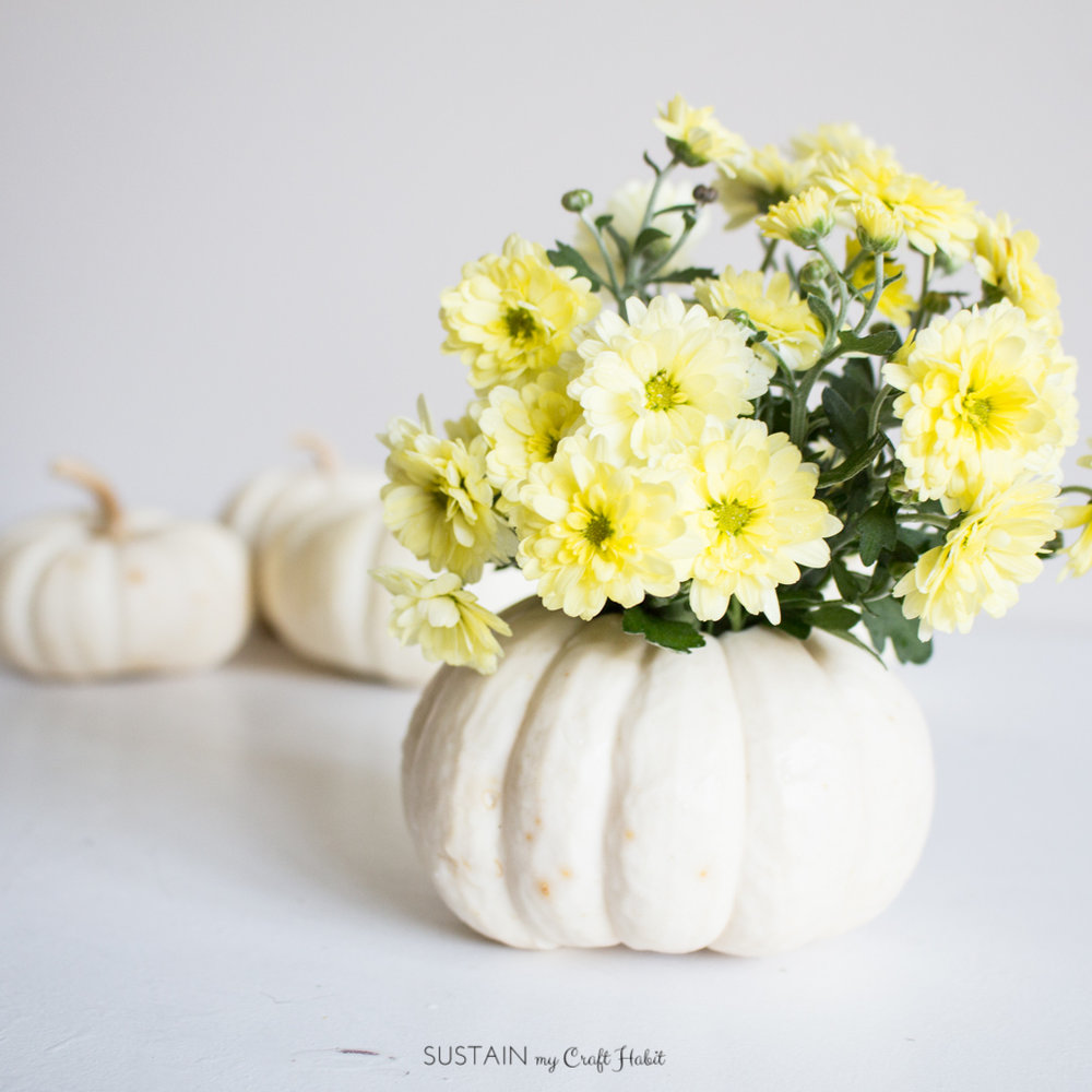 Make a simple and gorgeous centerpiece with mini white ghost pumpkins and fresh flowers. An easy and natural fall decor idea for your autumn entertaining.