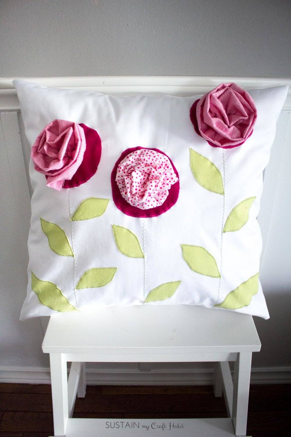 Such a thoughtful handmade gift idea for mom or grandma! DIY farmhouse inspired throw pillow upcycled from outgrown baby clothing. Click through for the full tutorial.